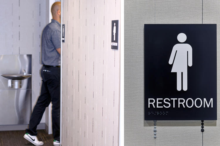 Image of man entering washroom beside image of gender neutral signage icon (Photo credit: Perkins + Will)