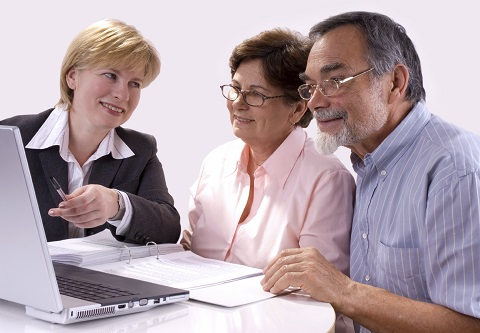 Older couple looking at laptop with their agent.